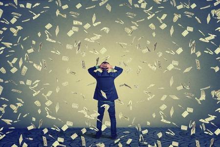 uomo sotto la pioggia: vista posteriore posteriore di uomo d'affari in piedi di fronte a un muro sotto le banconote di dollari di denaro pioggia caduta, le mani sulla testa chiedendo. Lunghezza totale del corpo di uomo d'affari di fronte al muro Archivio Fotografico