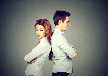 negative emotion: Angry frustrated young couple standing back to back. Side profile unhappy sad man and woman. Negative emotion face expression reaction