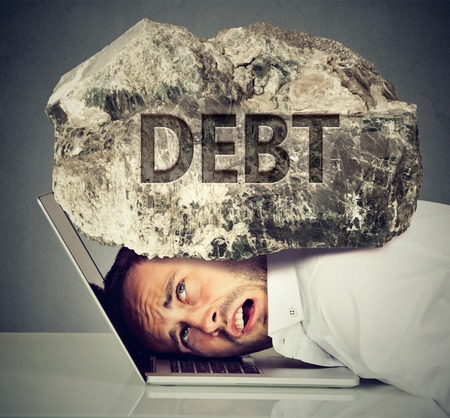 Young desperate business man with his head squeezed between laptop computer keyboard and  rock. Student university loan debt concept 免版税图像