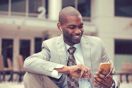 Young happy smiling urban professional man using smart phone listening to music. Businessman holding mobile smartphone using app texting sms message wearing suit