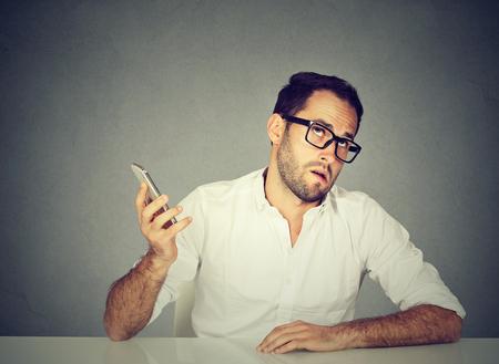 휴대 전화와 함께 근접 촬영 짜증이 젊은 남자. 긴 대기 시간, 끔찍한 대화 개념. 인간 감정 얼굴 표현 반응
