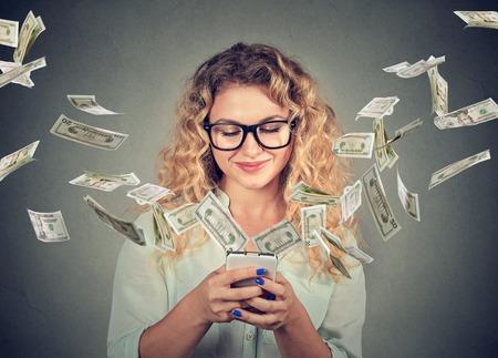 Technologie Online-Banking Geldtransfer, E-Commerce-Konzept. Glückliche junge Frau mit Smartphone mit Dollarnoten fliegen weg von Bildschirm isoliert auf grau Wand Hintergrund