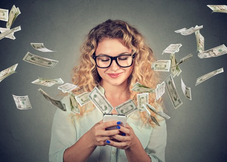 Technology online banking money transfer, e-commerce concept. Happy young woman using smartphone with dollar bills flying away from screen isolated on gray wall background