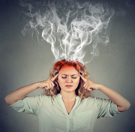 errands: Woman thinks very intensely having headache isolated on gray wall background Stock Photo