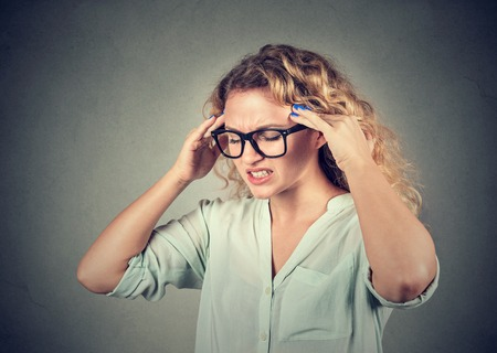 compulsive: Closeup portrait sad young woman in glasses with worried stressed face expression isolated on gray wall background. Obsessive compulsive, adhd, anxiety disorder. Stock Photo