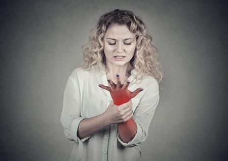 Jonge vrouw die haar pijnlijke pols over grijze muur achtergrond. Verstuiking pijn locatie aangegeven door rode vlek. Stockfoto - 64447217