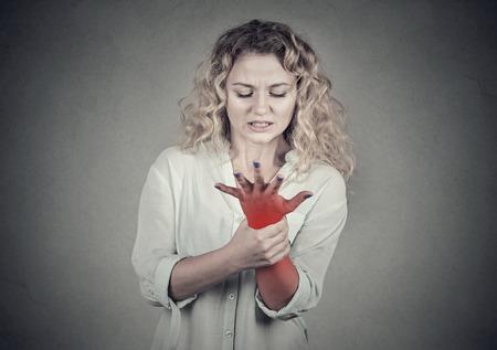 Young woman holding her painful wrist over gray wall background. Sprain pain location indicated by red spot.