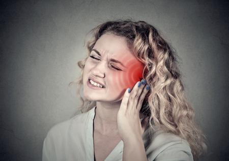 dolor de oido: Tinnitus. Portarretrato encima de perfil lado femenino enfermo que tiene dolor de oído tocar su dolor de cabeza aislado en el fondo gris Foto de archivo