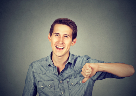 sarcastic: Closeup portrait sarcastic young man showing thumbs down sign hand gesture, happy someone lost isolated on gray background. Human emotion, facial expression, feelings attitude
