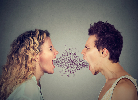 Side profile angry young couple man and woman screaming face to face with alphabet letters coming out of open mouth. Negative face expression emotion Banque d'images