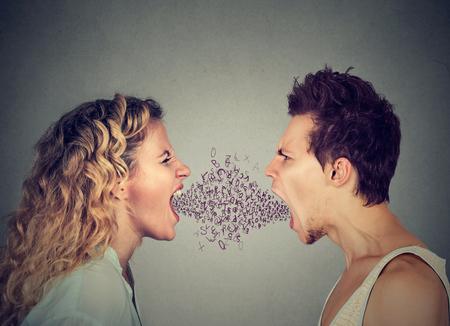 Zijprofiel boze jonge paar man en vrouw schreeuwen van aangezicht tot aangezicht met de letters van het alfabet coming out van open mond. Negatieve gezichtsuitdrukking emotie