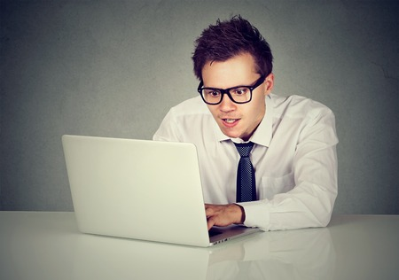 spammer: Man using his laptop computer sitting at table