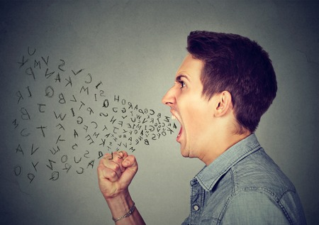 Side profile portrait of young angry man screaming with alphabet letters flying out of wide open mouth isolated on gray wall background