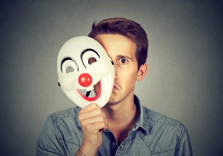 likable: Young sad man hiding behind happy clown mask isolated on gray wall background. Human emotions