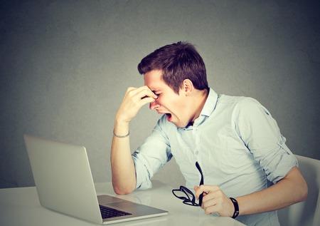 지친 느낌. 노트북 컴퓨터의 앞에 자신의 작업 장소에 앉아있는 동안 피곤 된 젊은 남자가 그의 코를 마사지하고 눈을 유지 폐쇄