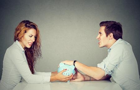 Financiën in echtscheiding concept. Vrouw en man kan geen schikking bedrijf spaarpot zitten aan tafel te kijken naar elkaar met haat Stockfoto