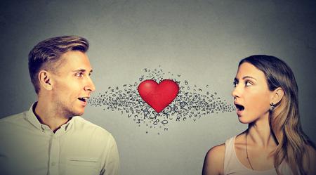 donna innamorata: L'amore di connessione. L'uomo la donna a parlare gli uni agli altri con cuore rosso nel mezzo e le lettere dell'alfabeto che esce dalla bocca aperta Archivio Fotografico