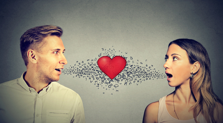 analogy: Love connection. Man woman talking to each other with red heart in-between and alphabet letters coming out of open mouth Stock Photo