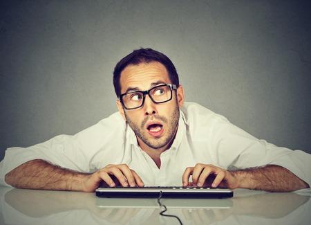 Hombre que pulsa en el teclado preguntándose qué responder Foto de archivo