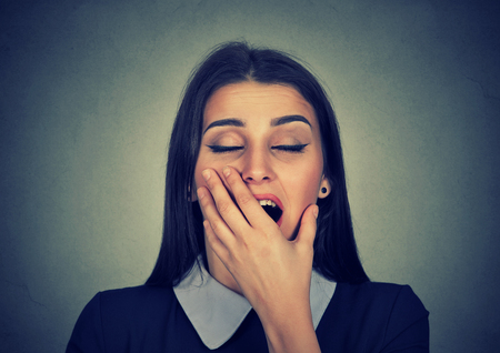 deprived: It is too early for meeting. Sleepy young woman with wide open mouth yawning eyes closed looking bored isolated on gray background. Face expression emotion body language Stock Photo
