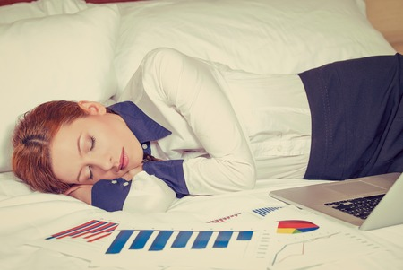 working hours: Businesswoman asleep on the bed, hotel or domestic room. Tired employee taking a nap. Long working hours