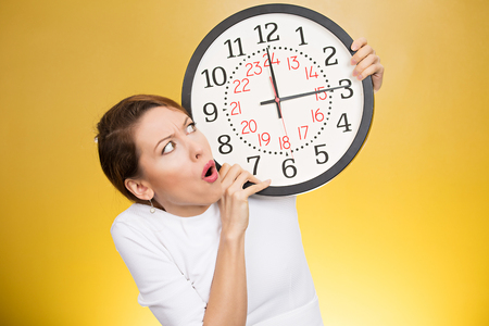 time out: Time pressure. Stressed woman holding clock looking anxiously running out of time isolated on yellow background. Human face expression emotion reaction. Last moment
