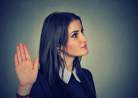 insulting: Closeup portrait young annoyed angry woman with bad attitude giving talk to hand gesture with palm outward isolated grey wall background. Negative human emotion face expression feeling body language