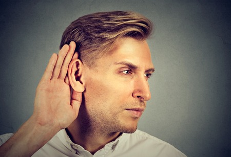 Side profile man holds his hand near ear and listens carefully isolated on gray wall background