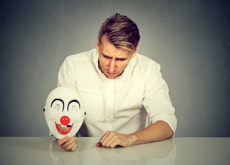Portrait young upset worried man with sad expression holding clown mask expressing cheerfulness happiness isolated on gray wall background. Human emotions feeling. Mental health concept