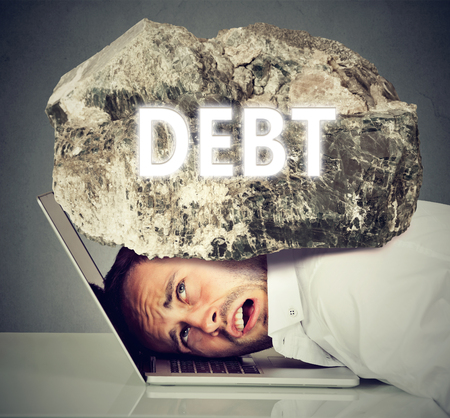 Young desperate business man with his head squeezed between laptop computer keyboard and  rock. Student university loan debt concept Banque d'images