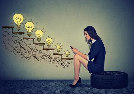 Bonne jeune femme assise sur une roue en face de la croissance des ampoules. Affaires succès de l'éducation, la promotion, le concept de croissance de l'entreprise. Affaires utilisant un téléphone portable