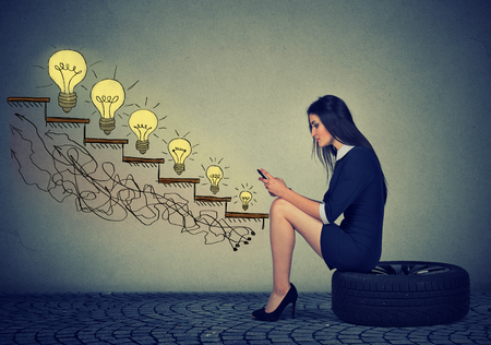 increase sales: Happy young woman sitting on a wheel in front of growing up light bulbs. Business education success, promotion, company growth concept. Businesswoman using mobile phone