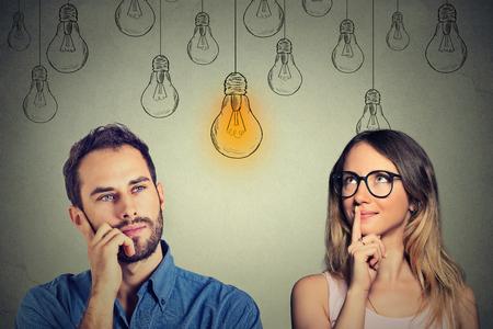 Kognitive Fähigkeiten Fähigkeit Konzept, männlich vs weiblich. Junger Mann und Frau, die am hellen Glühbirne suchen isoliert auf grau Wand Hintergrund