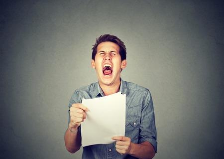 caras emociones: Tensionado enojado gritando hombre de negocios con los documentos papeleo papeles aislados sobre fondo gris pared de la oficina. Las emociones negativas se enfrentan a la expresión