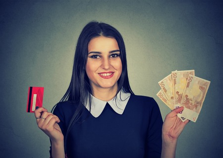 point: Young woman shopping holding showing credit card and cash fifty euro banknotes bills