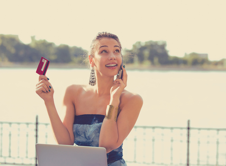 cash back: Woman talking on mobile phone placing online oder holding credit card and laptop sitting outside by the lake Stock Photo