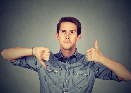 indecisiveness: Perplexed man with thumbs down thumbs up gesture