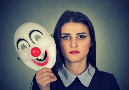 formalities: Young woman with sad face expression holding clown mask expressing cheerfulness happiness isolated on gray wall background