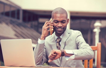 hear business call: Busy young business man working on laptop outdoors talking on mobile phone looking at his wristwatch. Time is money concept. Lifestyle of a successful happy deal maker