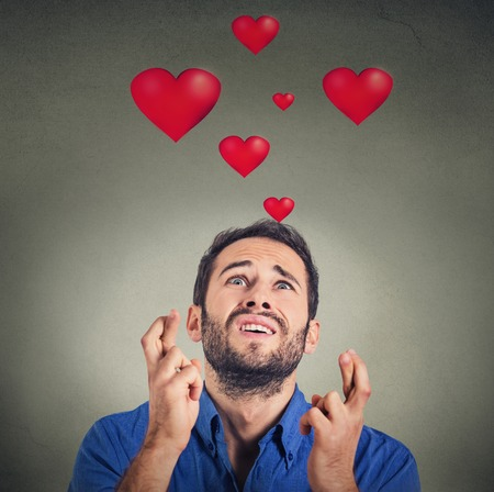 implore: Young man in love making a wish isolated on gray background with red hearts above head Stock Photo