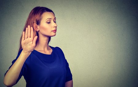 aggravated: Closeup portrait young annoyed angry woman with bad attitude giving talk to hand gesture with palm outward isolated grey wall background. Negative human emotion face expression feeling body language