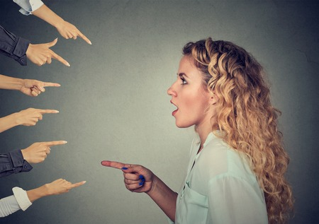 Concept of accusation guilty person woman. Side profile shocked girl pointing against many fingers isolated on grey wall background. Human face expression emotion feeling Stock Photo
