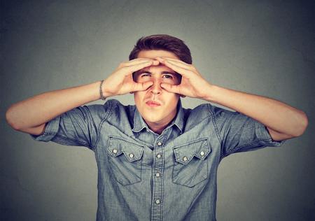displeased: Displeased young man looking through fingers like binoculars Stock Photo