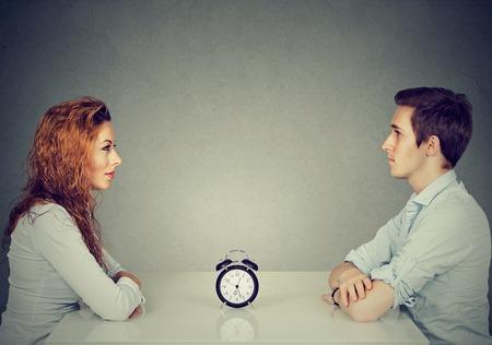 Citas rápidas. El hombre y la mujer que se sientan uno frente al otro en la mesa con el reloj de alarma en el medio