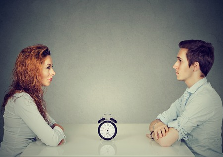 Speed dating. Man and woman sitting across from each other at table with alarm clock in-between Stok Fotoğraf