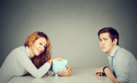 ex wife: Finances in divorce concept. Happy wife with piggy bank sitting across the table from sad desperate ex husband