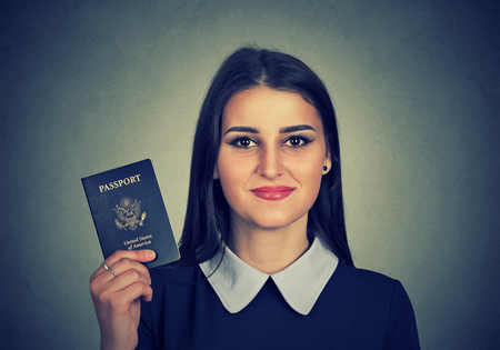 american content: Portrait attractive young happy woman with USA passport isolated on gray wall background. Positive human emotions face expression. Immigration travel concept Stock Photo