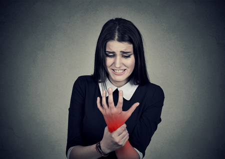 degenerative: Young woman holding her painful wrist colored in red  isolated on gray wall background. Sprain pain