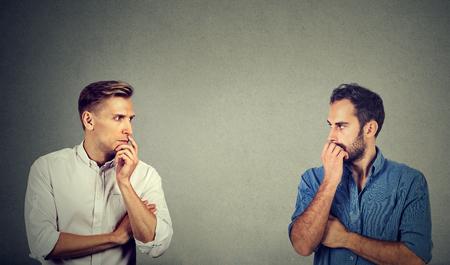 profiel van twee gepreoccupeerde zakenlui die naar elkaar kijken