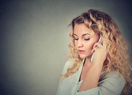 Young sad woman talking on mobile phone